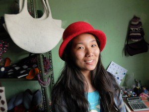 Pema models a hat in her aunty's craft shop.